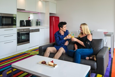 A picture of a couple having a drink in the hotel room at Adge Hotel on Riley Street in Sydney