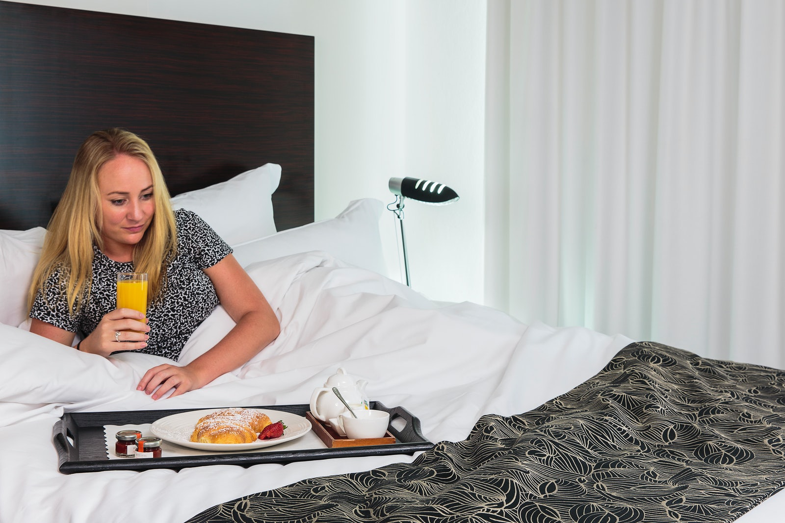 A picture of a woman having breakfast in bed at the Cambridge Hotel in Surry Hills Sydney